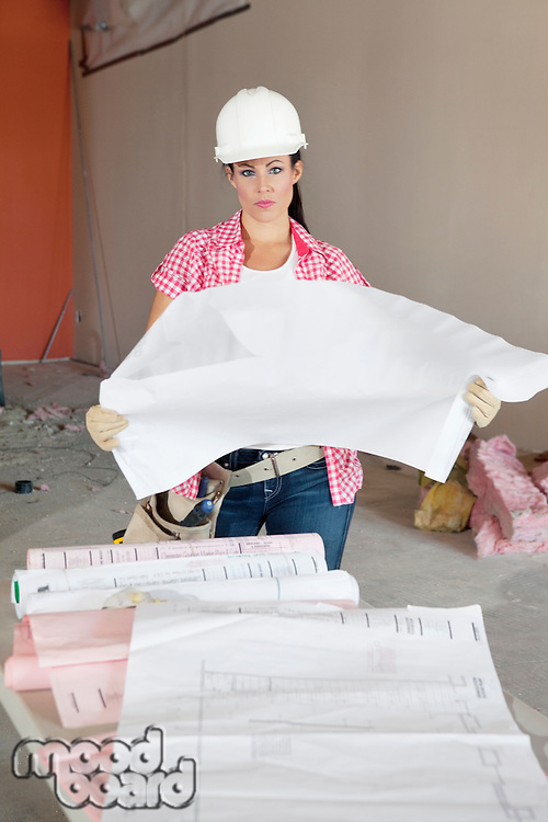 Portrait of serious female architect holding building plans at construction site