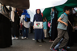 London, UK. 10th June, 2018. A girl stands with a 'Free Palestine' sign underneath a giant Palestinian flag being held up outside the Saudi embassy before hundreds of people take part in the pro-Palestinian Al Quds Day march through central London organised by the Islamic Human Rights Commission. An international event, it began in Iran in 1979. Quds is the Arabic name for Jerusalem.