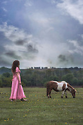 a woman with a pony on a paddock