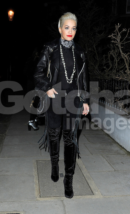Singer Rita Ora wearing a leather bikers jacket, sheer top, black velvet trousers and knee high boots out in south west London, UK. 06/03/2015<br />