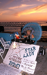 Key West, FL:  A wide variety of buskers such as this musician-astrologist perform nightly to the crowd awaiting sunset and the fabled green flash at Mallory Square Pier.