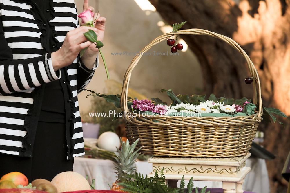 Florist arranges a flower bouquet in a basket