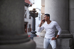 January 25, 2019 - Young man standing leaning against pillar making smartphone call, Cape Town, Western Cape, South Africa (Credit Image: © Cultura via ZUMA Press)