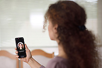 Woman with Apple iPhone X in her hand setting up Face ID, biometric authentication, by scanning her face with a new depth sensing camera from various angles