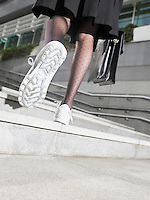 Business woman wearing running shoes walking up steps low section low angle view back view