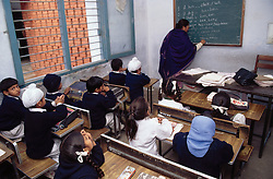 School girls and boys sitting at desks watching female teacher writing on whiteboard in senior secondary modern school; Punjabi University; Patiala; Punjab; India,