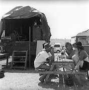 People sitting and drinking around a table, Glastonbury, Somerset, 1989