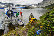 Alan Schmidt, Dave Costello and Parker Meek unload their gear at Ptarmigan Lake from a float plane in the Tweedsmuir National Park, BC, Canada