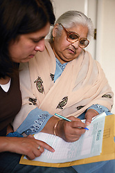Community support worker helping South Asian lady fill in a form,