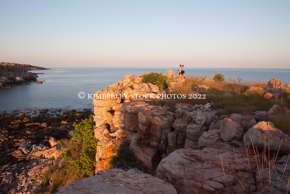 A photographer stands on Hall Point in Camden Sound to catch the sunrise.