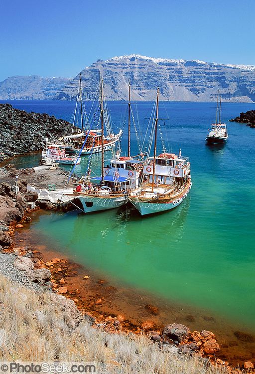"Tour boats moor in the harbor of active volcanic island Nea Kameni, in the southern Aegean Sea, Greece. The town of Fira perches on 700-foot-high volcanic cliffs on Santorini Island to escape summer heat and pirates of the past. Geologic and human history of Santorini: Humans first arrived around 3000 BC on this volcano known in ancient times as Thira (or Thera). The island was a volcanic cone with a circular shoreline until 1646 BC, when one of earths most violent explosions blasted ash all over the Mediterranean, sunk the center of the island, launched tidal waves, and may have ruined the Minoan civilization 70 miles away on Crete. Remarkably, volcanic ash dumped onto the volcanos flanks actually preserved the village of Akrotiri and its 3600-year-old frescoes from the Minoan era. These are some of the earliest known examples of world art history, which you can now view in museums. In 286 BC, the volcano split off Thirasia (Little Thira) Island (to the West). The volcano began rebuilding, and in 197 BC the small center islet of Palia Kameni appeared. In 1707 CE, lava started forming Nea Kameni, the larger center island which erupted as recently as 1956 and caused a huge earthquake (7.8 on the Richter scale) which destroyed most of the houses in the towns of Fira and Oia. Fira and Oia have since been rebuilt as multi-level mazes of fascinating whitewashed architecture, attracting tourists from around the world. Published in ""Sparks"", the newsletter for the Museum of Science, Boston February/March 2006."