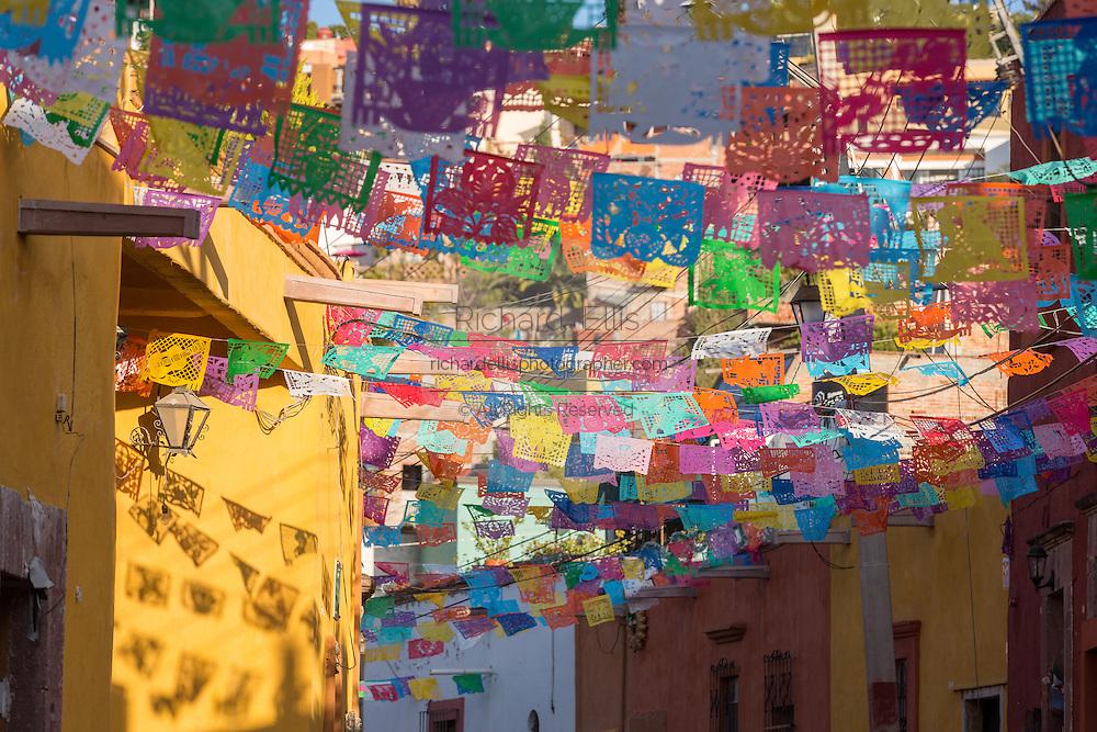 Festive papel picado banners decorate Calle Aparicio in the historic center of San Miguel de Allende, Mexico.