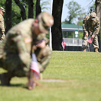 Sgt. 1st Class Carl Ethridge of the 834th Aviation Support Battalion helps place flags on the graves of veterans at Tupelo Memorial Park in Tupelo.