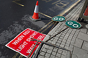 Two GO and Wait traffic road signs lie by the kerb on the ground in East Dulwich, on 26th April 2018, in London, England.
