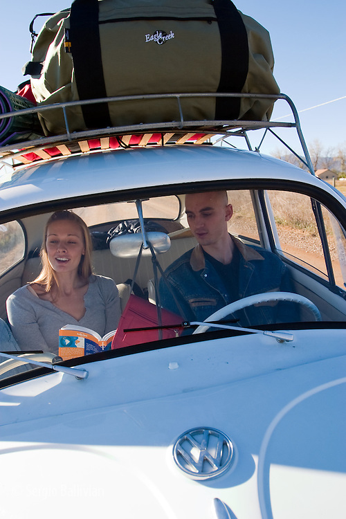 A young couple in a VW bug loaded with luggage drive through the backcountry near Denver, Colorado