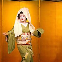 Asia, Japan, Kyoto. A geisha dances to entertain dinner guests.