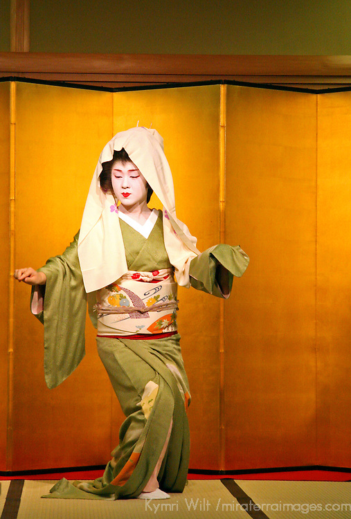 Asia, Japan, Kyoto. A geisha dances to entertain dinner guests.