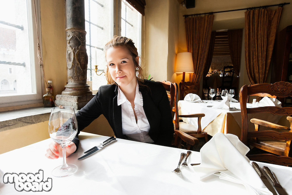 Portrait of beautiful customer with wine glass at restaurant table