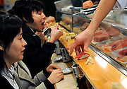 Customers enjoy tuna sushi at a hole-in-the-wall eatery located in the grounds of Tsukiji Fish Market.