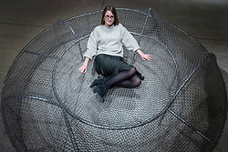 """© Licensed to London News Pictures. 06/11/2018. LONDON, UK. A staff member sits on """"Frame 03"""", 2017, by SO-IL.  Preview of """"Home Futures"""", at the Design Museum.  The exhibition, in partnership with IKEA Museum Almhult, asks are we living in the way that pioneering architects and designers once predicted, or has our idea of home proved resistant to real change?  More than 150 objects and experiences are on display 7 November to 24 March 2019.  Photo credit: Stephen Chung/LNP"""
