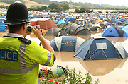 A Policeman taking a photograph of tents in a flooded campsite, Glastonbury 2005