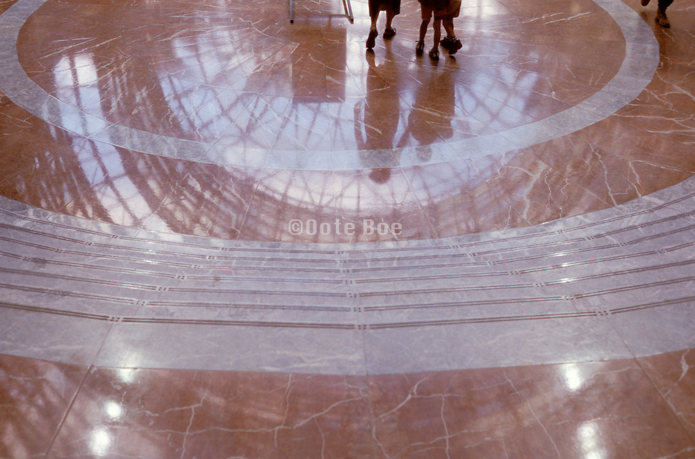 Reflections of people walking on a marble floor