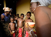 An elderly woman prepares to spread a concoction of ground millet and water - a symbol of protection - on the body of young girls from the Krobo tribal group undergo puberty rites - locally called dipo - in Somanya, Eastern Region, Ghana.