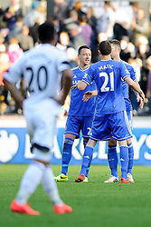 John Terry (ENG) of Chelsea smiles as Chelsea players celebrate but look relieved to secure an unconvincing 0-1 win, and Michel Vorm (NED) of Swansea looks on dejected  - Photo mandatory by-line: Rogan Thomson/JMP - 07966 386802 - 13/04/2014 - SPORT - FOOTBALL - Liberty Stadium, Swansea -  Swansea City v Chelsea FC - Barclays Premier League.