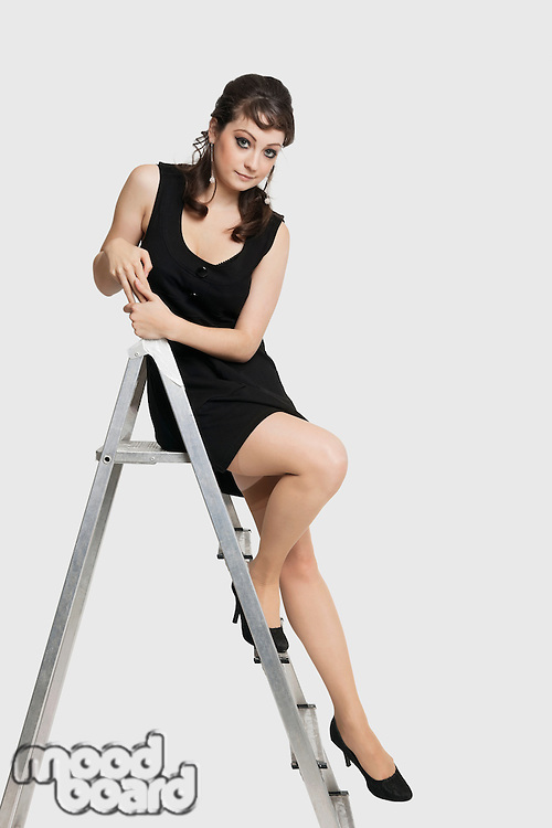 Portrait of beautiful young woman in dress sitting on step ladder against white background