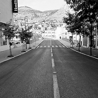 MOSTAR, BOSNIA AND HERZEGOVINA - JUNE 26:  A black and white image of the way leading to Tito Bridge with the Bristol Hotel on the left on  June 26, 2013 in Mostar, Bosnia and Herzegovina.The Siege of Mostar reached its peak and more cruent time during 1993. Initially, it involved the Croatian Defence Council (HVO) and the 4th Corps of the ARBiH fighting against the Yugoslav People's Army (JNA) later Croats and Muslim Bosnian began to fight amongst each other, it ended with Bosnia and Herzegovina declaring independence from Yugoslavia.  (Photo by Marco Secchi/Getty Images)