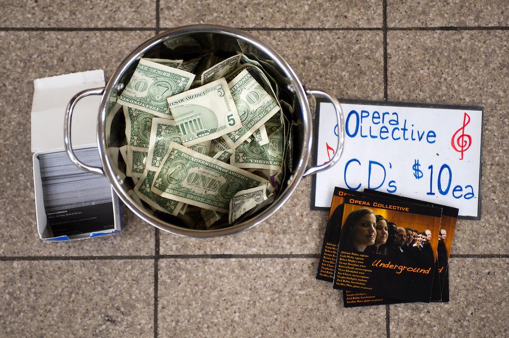 """Geldsammeltopf der """"Opera Collective"""" im Union Square Station. Sie sind offiziele Musiker von 'Music Under New York'...Jedes Jahr im Mai laden die Betreiber der New Yorker Subway (MTA) ca 60 Musiker und Gruppen zu einem Wettberwerb im Grand Central Station ein. Die Gewinner duerfen ganz legal an ihnen zugeteilten Orten im Ubahn System auftreten. Viele unangemeldete  und selbst organisierte Musiker jeder nur erdenklichen Musikrichtung spielen zudem in fast jeder wichtigen Ubahnstation. Die Angst vor der Polizei ist dabei gering, selten gibt es eine Verwarnung und noch seltener ein Bussgeld. Meist wird einfach der Ort gewechselt falls es Probleme gibt...MTA (Metropolitan Transportation Authority) .Music Under New York.Auditions.Every Spring, Music Under New York (MUNY) presents a day of auditions in Grand Central Terminal to review and add new performers to the MUNY roster. This year, MUNY held its annual auditions in May on the Northeast Balcony of the Grand Central Terminal. .In addition legions of non-official musicians play in New Yorks subway stations and on platforms. One can find every thinkable style and instrument underground. ..Foto: Stefan Falke."""