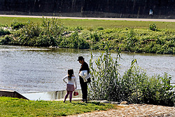 Barcelona, Catalunya,Spain. A man talking with a girl at the riverside Besos.© Carmen Secanella