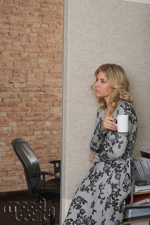 Woman leaning against bookcase with mug in office