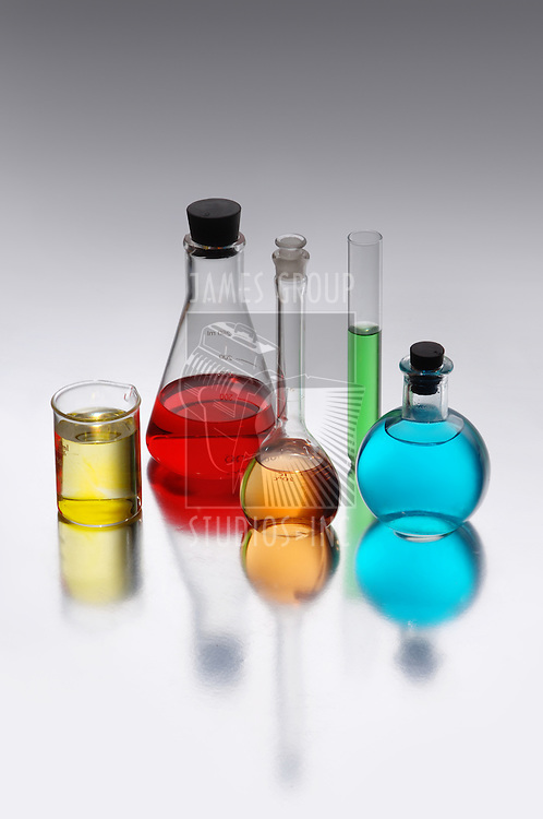 Chemical flasks with brightly colored liquids shot on a reflective surface