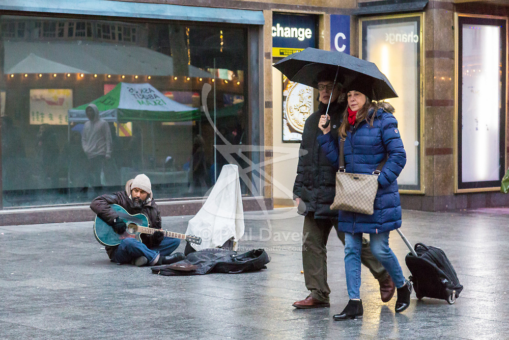 London, December 31 2017. The umbrellas come out as a downpour begins in London's west end ahead of the New Year's Eve fireworks at midnight. PICTURED: A couple sharing an umbrella walk past a busker as the rain begins to fall in Leicester Square. © SWNS