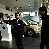BEIJING, APRIL-22, 2010:  a sales assistant receives a customer at the  BMW dealership .