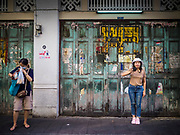 "26 FEBRUARY 2019 - BANGKOK, THAILAND: A woman poses for photos against a weathered wall in Bangkok's Chinatown. Bangkok has one of the largest ""Chinatown"" districts in the world. About 14% of all Thais have some Chinese ancestry and Chinese cultural practices are incorporated in many facets of Thai daily life.       PHOTO BY JACK KURTZ"