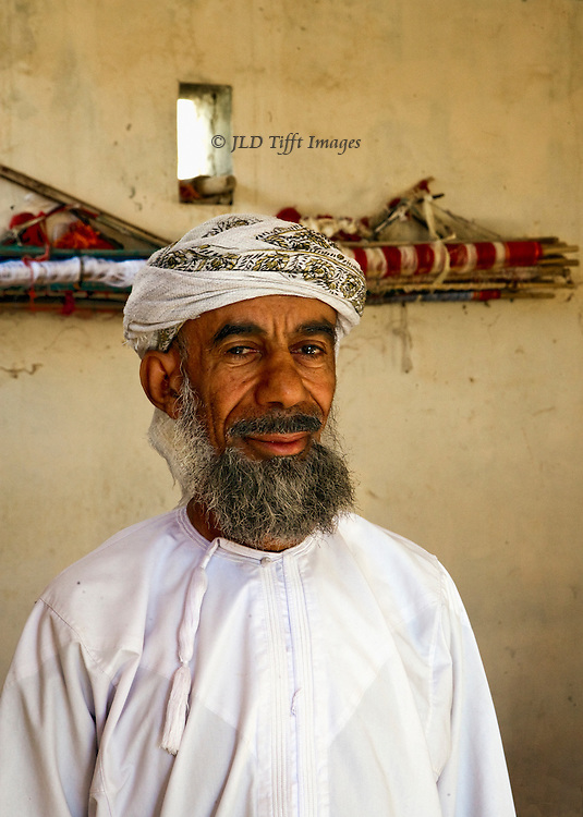 Oman, village of Samad, home of traditional pit weavers. Portrait of elderly bearded man in traditional dress of white dishdasha and wrapped turban.  He smiles enigmatically.