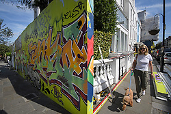 © Licensed to London News Pictures. 23/08/2019. London, UK. A woman walks her dog past graffiti covered boards outside the Paul Smith store, as preparations begin in Notting Hill, West London ahead of the 2018 Notting Hill Carnival which starts this weekend. Warm weather is expected over the bank holiday weekend with carnival attracting over 1 million people to the capital. Photo credit: Ben Cawthra/LNP