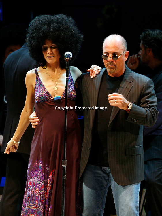 Singers Sheryl Crow(L), wearing a wig, and Billy Joel(R) perform during the finale of the Rainforest Foundation's benefit concert in New York May 19, 2006. REUTERS/Keith Bedford