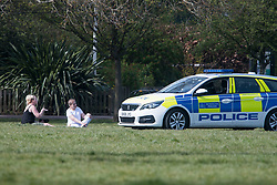 © Licensed to London News Pictures. 07/04/2020. London, UK. Police in a patrol car moving people who are sunbathing and sitting in Queens Park, north west London, during a pandemic outbreak of the Coronavirus COVID-19 disease. The public have been told they can only leave their homes when absolutely essential, in an attempt to fight the spread of coronavirus COVID-19 disease. Photo credit: LNP