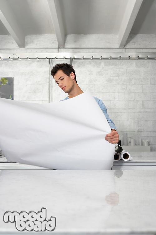 Man Looking at Building Plan