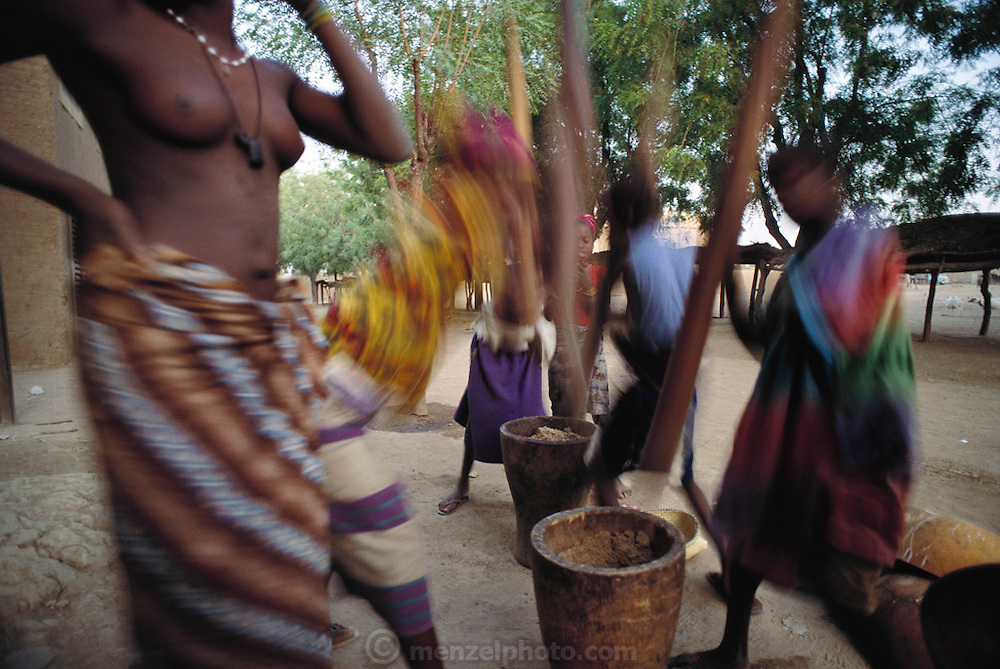 Women and girls pound millet grain to make flour for porridge in Djenne, Mali. Talking and singing often accompany this very physical task. Published in Material World: A Global Family Portrait, page 16.