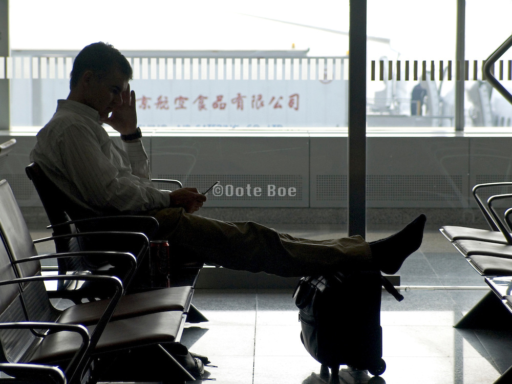 person making a text message while waiting at the airport in Beijing China