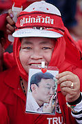 "Mar. 26, 2009 -- BANGKOK, THAILAND: A woman holds up a photo of ousted Thai Prime Minister Thaksin Shinawatra at a rally in Bangkok. More than 30,000 members of the United Front of Democracy Against Dictatorship (UDD), also known as the ""Red Shirts""  and their supporters descended on central Bangkok Thursday to protest against and demand the resignation of current Thai Prime Minister Abhisit Vejjajiva and his government. Abhisit was not at Government House Thursday. The protest is a continuation of protests the Red Shirts have been holding across Thailand in March.  Photo by Jack Kurtz"