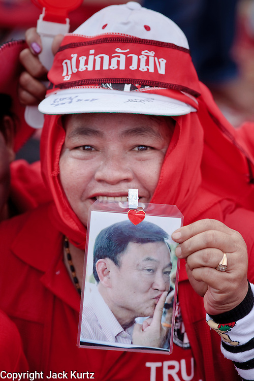 """Mar. 26, 2009 -- BANGKOK, THAILAND: A woman holds up a photo of ousted Thai Prime Minister Thaksin Shinawatra at a rally in Bangkok. More than 30,000 members of the United Front of Democracy Against Dictatorship (UDD), also known as the """"Red Shirts""""  and their supporters descended on central Bangkok Thursday to protest against and demand the resignation of current Thai Prime Minister Abhisit Vejjajiva and his government. Abhisit was not at Government House Thursday. The protest is a continuation of protests the Red Shirts have been holding across Thailand in March.  Photo by Jack Kurtz"""
