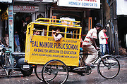 Delhi, India, the main bazaar street, school transportation a bicycle rickshaw