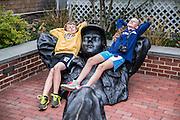 Siblings relax with a sculpture, Edgartown, Martha's Vineyard, Massachusetts, USA