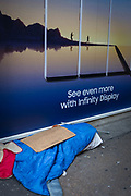 The possessions of a homeless person beneath an aspirational ad for Samsung's Infinity Display and a paradise lifestyle, on 22nd November 2017, in London England.