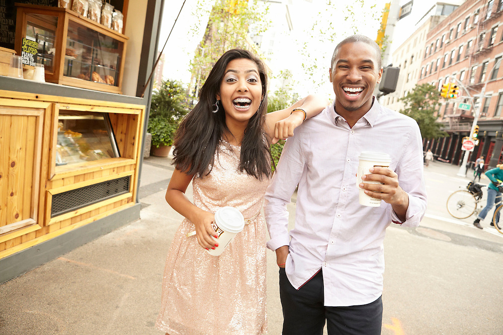 Lifestyle image of Indian and African American couple with coffee laughing outside